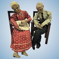 (2) Quality Antique Knitting Grandparent Wax Doll Pair in Wooden Chairs