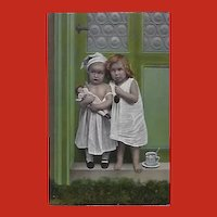 Glossy German Photo Postcard of Children with Doll and Pipe