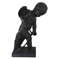 Antique 19th century Black Painted Zinc Lead Garden Ornament Statue of the Winged Angel Cupid or Cherub with a Drawknife Adze Fashioning His Bow Symbolizing Love
