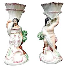 Antique Early 19th century English George III Staffordshire Pearlware Figures of Venus and Cupid in the Rococo Taste Each Holding a Cornucopia Vase