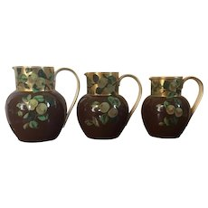 Group of Three Graduated English Aesthetic Movement Pottery Pitchers or Jugs Decorated with Hand Painted Fruit Peach Quince Branches on Brown and Gold Ground