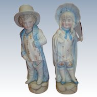 "Cute Pair of Antique Bisque Figurines of Boy and Girl Playing ""Dress Up"""