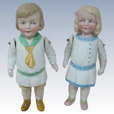 Large All Bisque German Boy and Girl Pair with Molded Clothes, Jointed Arms, Side Glancing Eyes