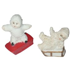 2 Old German Snow Babies 1 Standing on Red Sled 1 Sitting on Brown Sled