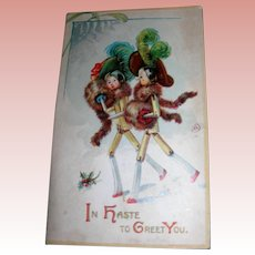 Christmas Postcard of Wooden dolls with Christmas Hats in plastic cover