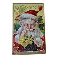 Santa With Hand To Nose Embossed Christmas Postcard With Present In Hand