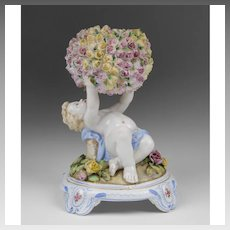 German Porcelain Figurine of Cherub Holding Flower Encrusted Globe