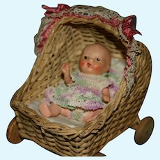 Adorable little wicker buggy and painted bisque baby