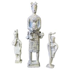 """3 piece set of Ashanti bronze figures. Tallest figure is 8"""" tall x 1 1/2"""" wide. She is offering a pineapple and has bells at her waist. The other 2 figures appear to be hanging or about to be hung from gibbet and measure approximately 4 1/2"""" tall x 1"""
