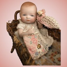 """Thank you 'S'_5"""" All Bisque Glass-eyed Bye-Lo Baby in Primitive Wicker Bed_Swivel head w/Blue Shoes_Grace S. Putnam_c. 1925 Germany."""