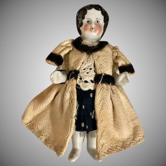 Antique German Frozen Charlotte all China doll delightfully dressed in 3 pc outfit.