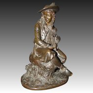 Antique French bronze sculpture of seated man playing the bagpipes