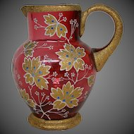 Cranberry gilded and enameled art glass pitcher flowers leaves