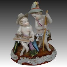 German porcelain figurine cupids seated artist painting a picture blue mark