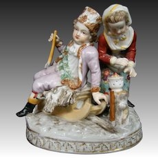 Dresden Germany porcelain figurine boy on sled girl at fire