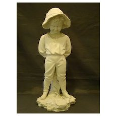 Parian ware large figurine of young boy sticking tongue out