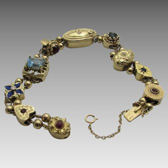 14 Karat Yellow Gold Slide Bracelet With 9 Unique Charms Most With Gemstones