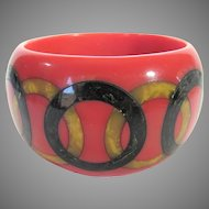 Bakelite Peach Bangle With Complex Inlaid Pattern of Black and Butterscotch Marbled Rings