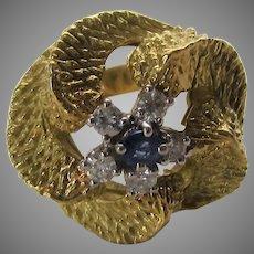 18 Karat Yellow Gold Swirls Around a Single Sapphire Surrounded by Diamonds