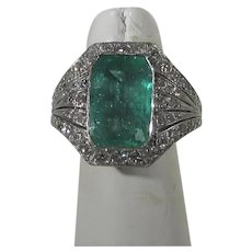 Six Carat Columbian Natural Emerald Surrounded by Pave Diamonds in  10 Karat Deco White Gold Setting