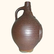Stoneware Jug with face and logo in relief