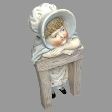 German All Bisque Molded Bonnet Doll on Fence