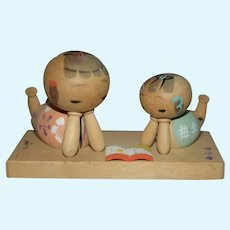 Two Vintage Japanese Wood Kokeshi Dolls Sitting on Platform