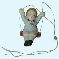 Antique porcelain boy swinger