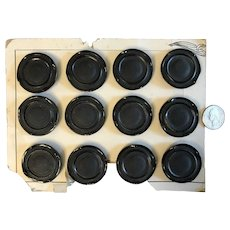 12 One inch vintage scalloped black buttons on cardboard