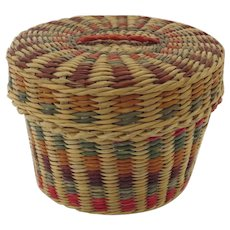 Vintage small sweetgrass basket with lid, handwoven, from the 1960s, has natural pigment dye accents of cranberry red and forest green and a braided handle on the lid.