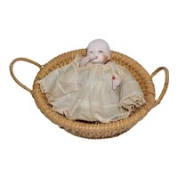 "4"" German Bisque Baby with Molded Bottle in a Basket"