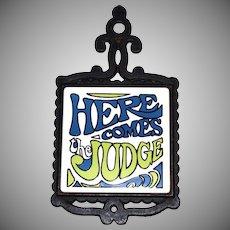 1960s 'Here Comes The Judge' White Ceramic Tile & Black Cast Metal Kitchen Trivet