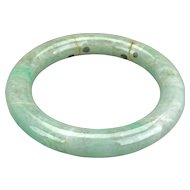 Chinese pale green jade 55 mm bangle with apple green spotting late 19th early 20th century