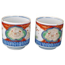 Matched pair of Japanese porcelain colored Imari teacups with shi shi design Meiji Period