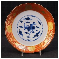 Japanese Meiji era (1868-1912) Kutani plate with central crane in blue and white with floral border in red and gold