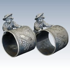 Matched pair of Victorian silver plate napkin rings of boys pushing barrels circa 1870