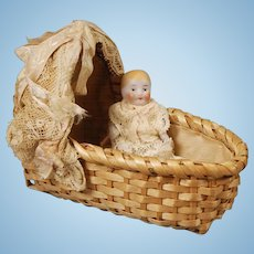 German Jointed Bisque Baby with Reed Cradle