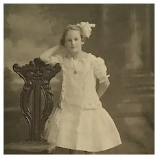 Matted Photograph-  Girl Wearing White Ruffled Dress, Locket And Hair Bow