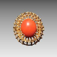 Fourteen karat yellow gold ring with a tomato red coral cabochon in the center