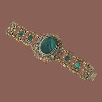 An Ornate Brass Filigree Bracelet With Green Enamel And Glass Stones, Circa 1920