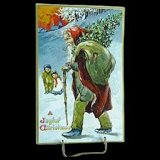 1909 Embossed Christmas Postcard Santa In A Brown Robe With Tree & Sack Of Toys Tuck