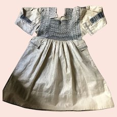 Circa 1900.Childs smock hand worked in line with blue embroidery .