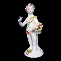 An English Bow Porcelain Figure Of A Putti Holding A Basket Of Fruit, c.1760
