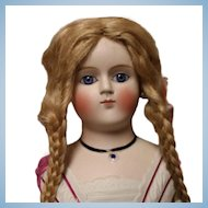 Porcelain doll head on cloth and leather body, stands 18 inches tall..human hair wig, blue set glass eyes