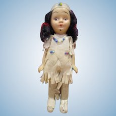 Small unusual frozen charlotte all bisque Native American doll in paper outfit with beads old 5""