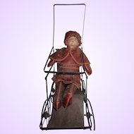 Very old stroller with oil cloth and bisque doll caped little red