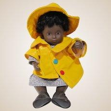 Small dark Sasha baby doll in original dress with rain gear