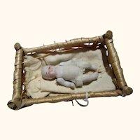 Vintage Japan bisque miniature baby in straw crib