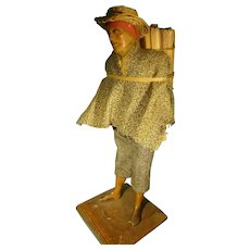 """9 1/2"""" Poured Wax Man Carrying Wood"""