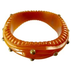 Vintage Carved Bakelite Bangle with Brass Studs in Marbled Butterscotch Amber